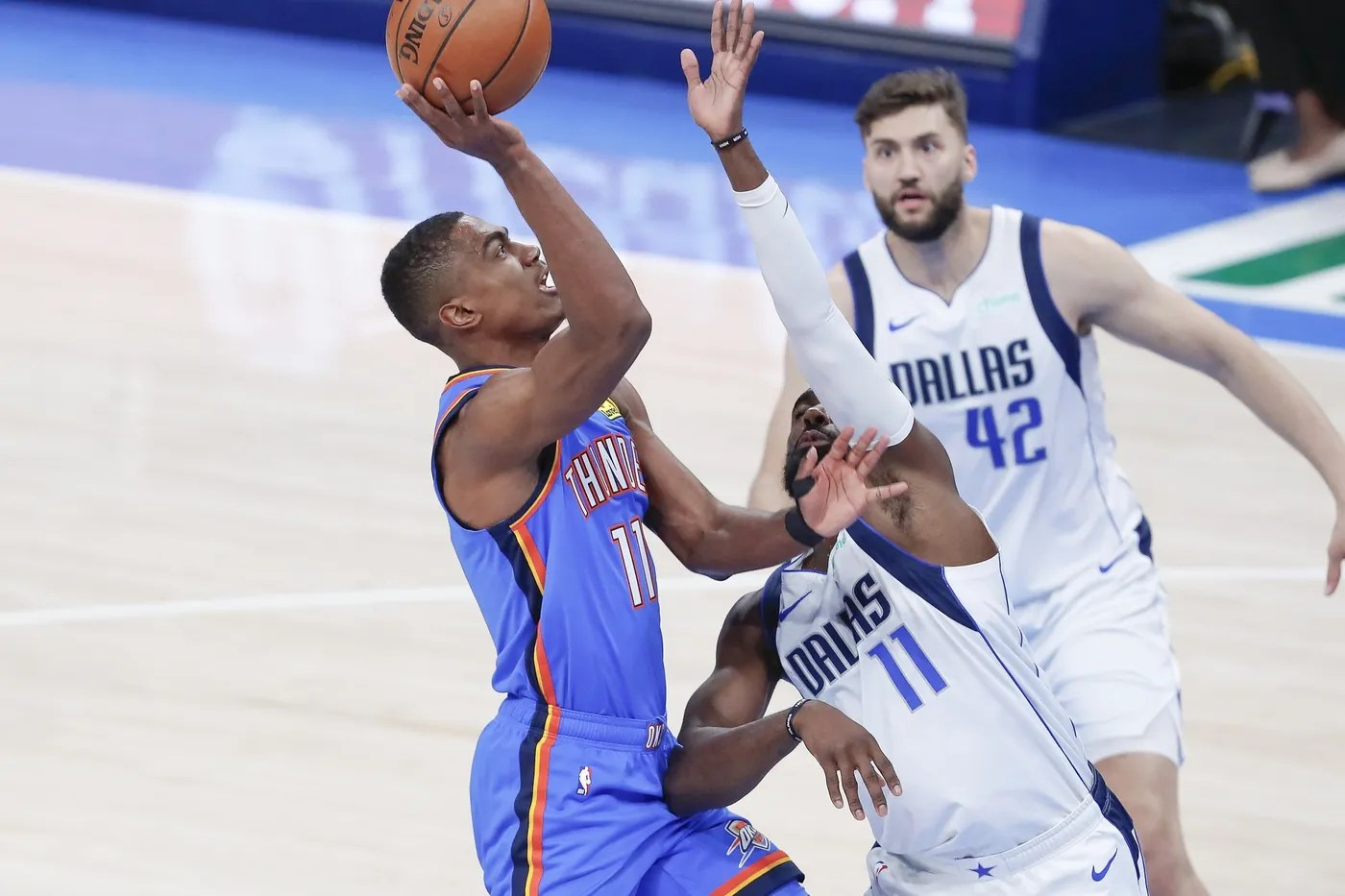 Mar 29, 2021; Oklahoma City, Oklahoma, USA; Oklahoma City Thunder guard Theo Maledon (11) goes up for a shot as Dallas Mavericks forward Tim Hardaway Jr. (11) defends him during the second quarter at Chesapeake Energy Arena. Mandatory Credit: Alonzo Adams-USA TODAY Sports