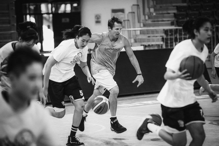 Live Training with Ganon Baker Basketball Skills and Development - Ganon Baker running with a group on a basketball court
