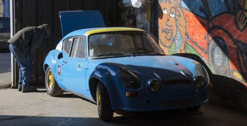 La Simca CG 1300 en réparation au garage attire la curiosité des passants