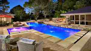 overall shot of backyard with baja shelf contemporary style pool, firewall, seating area, and gym in background