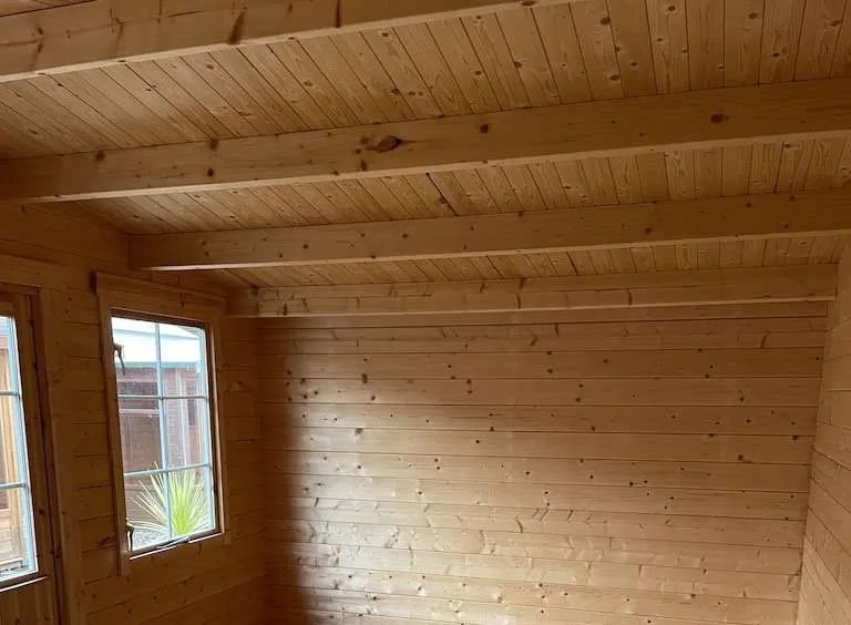 Exposed timber log cabin interior.