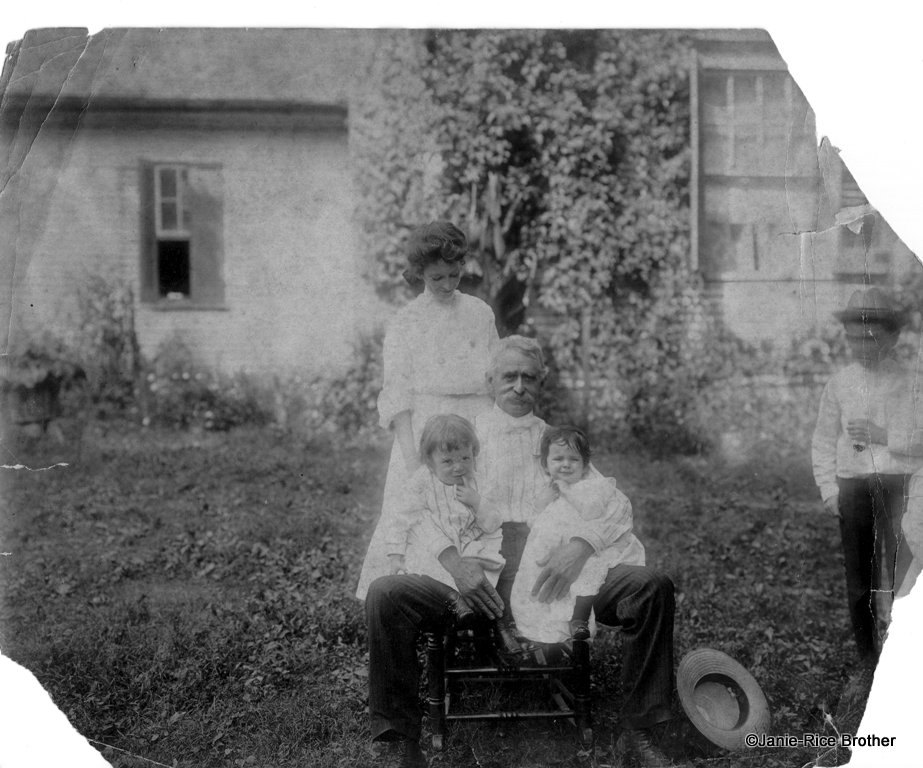 My great-grandmother (standing), my great-great-grandfather, and in his lap, my great-uncle and my grandmother.