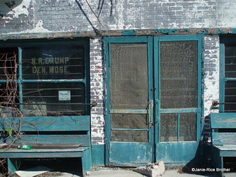 The store had double doors, and benches on either side in front of the large display windows.