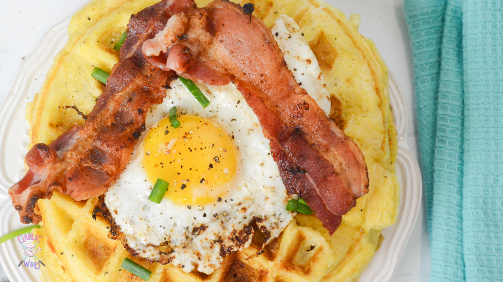 Waffles with a fried egg and bacon on top.