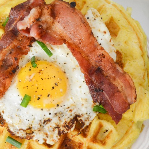 fried egg on top of a waffle with strips of bacon