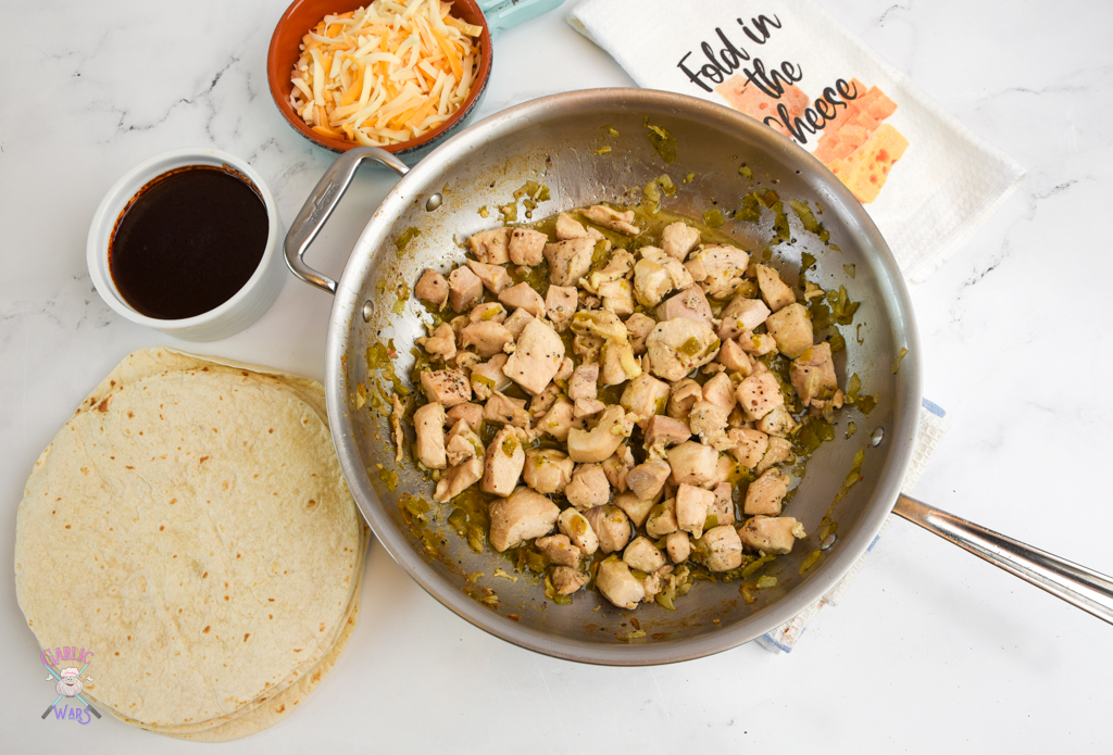 """large pan with cooked chicken, with enchilada sauce, tortillas, cheese, and a tea towel that reads """"fold in the cheese"""""""