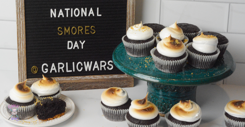 """cupcakes on a teal cake stand, with more on the surrounding table, with a black letter board sign that reads """"national smores day"""""""