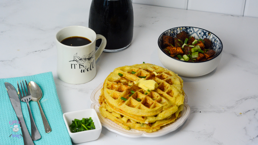 A place setting with a cup of coffee, a bowl of sweet potato home fries, and a plate of waffles.