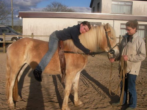 Kind auf Pferd beim Therapeutischen Reiten