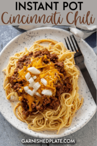 It may not really be chili, but it's delicious none the less! Enjoy this easy Instant Pot Cincinnati Chili over steaming spaghetti noodles and topped with plenty of melty cheese. Onions optional! #instantpot #cincinnatichili #pasta