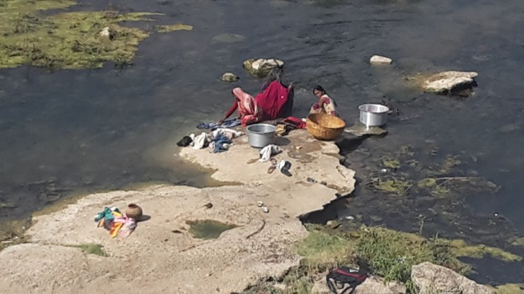 Indian women washing clothes in a stream