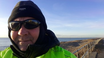 Man in cold weather clothes on the seafront