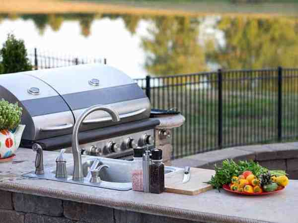 Preparing a healthy summer meal in an outdoor kitchen with gas barbecue and sink on a brick patio overlooking a tranquil lake with tree reflections