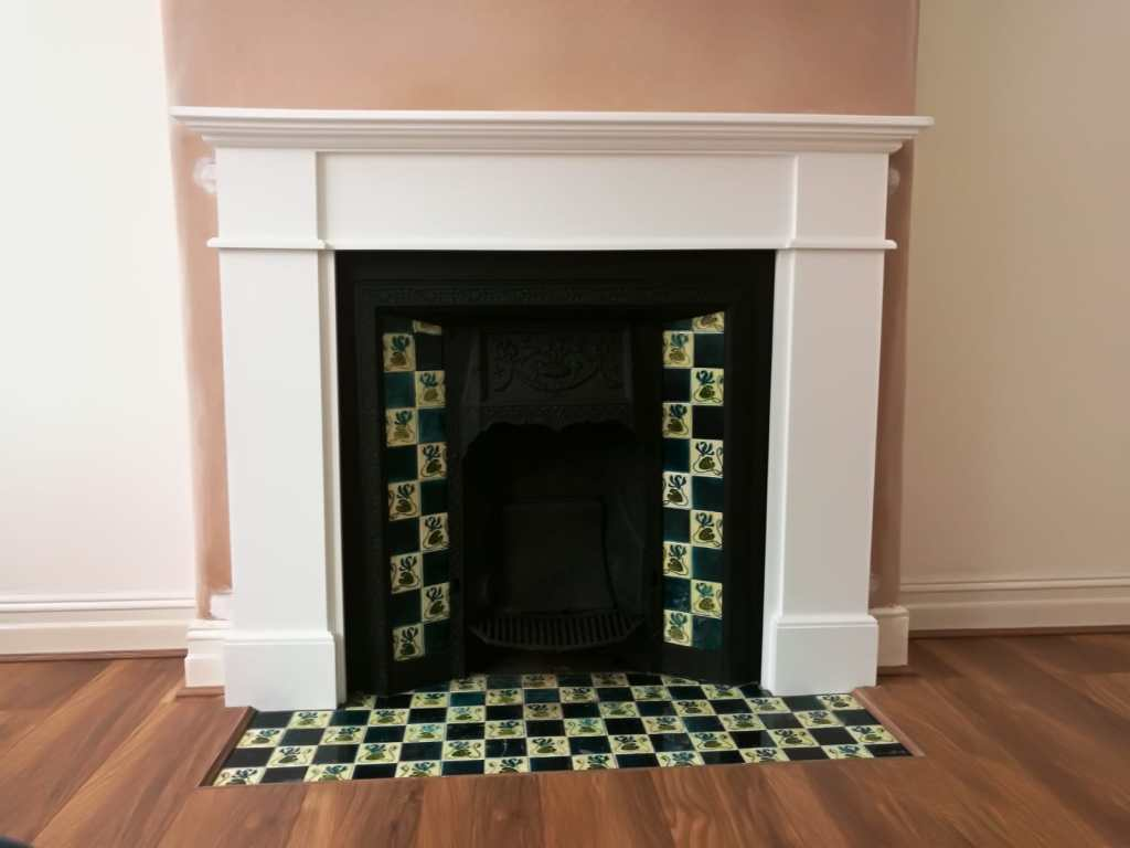 Restored cast iron tiled fireplace with new wooden mantel