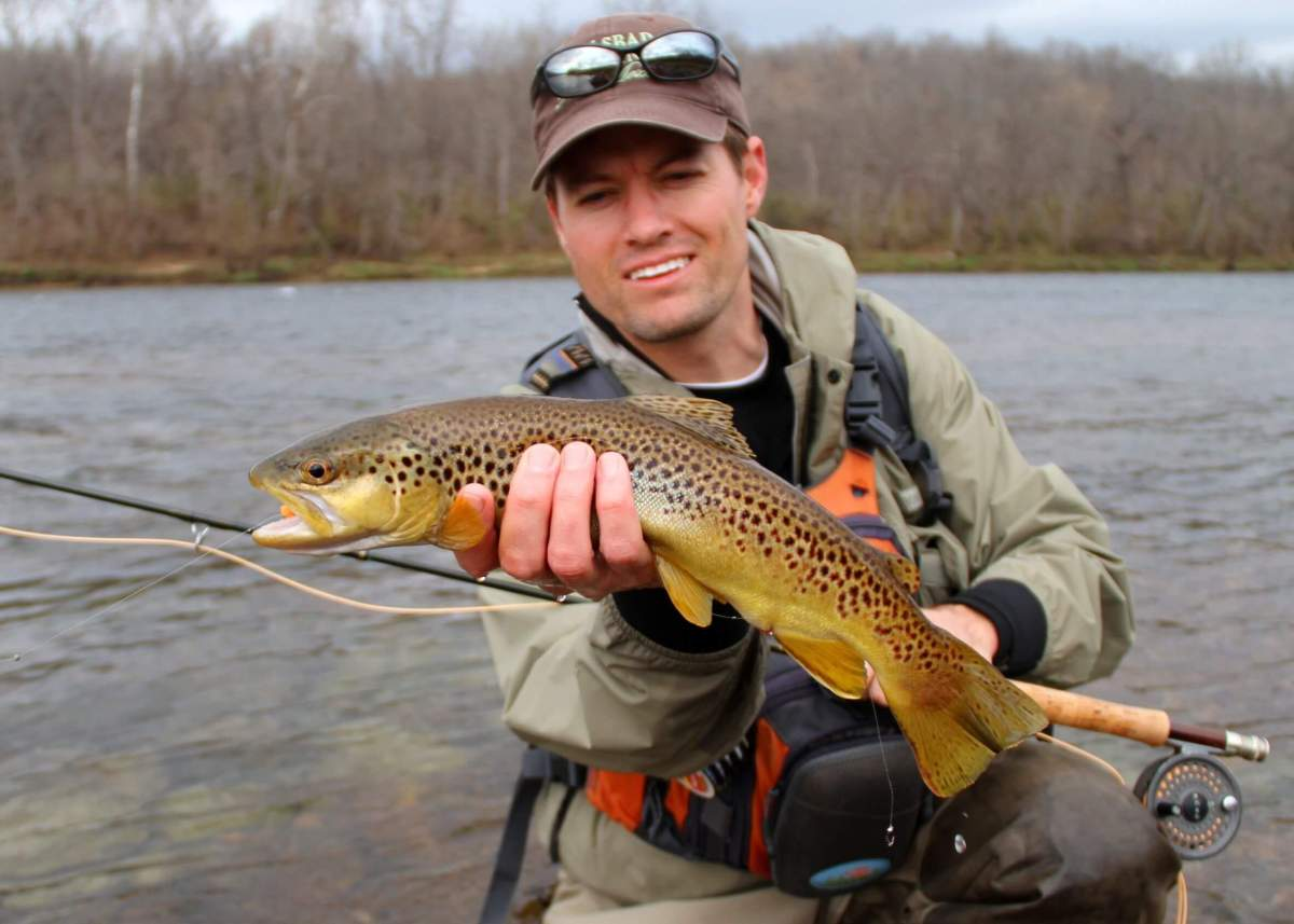 A proud angler hoists his brown trout bounty.