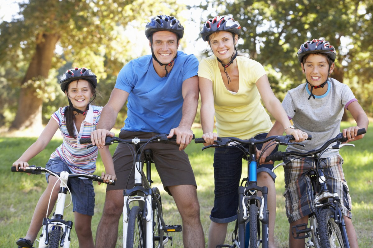 A joyous family smiles with excitement as they get ready to go mountain biking in Arkansas