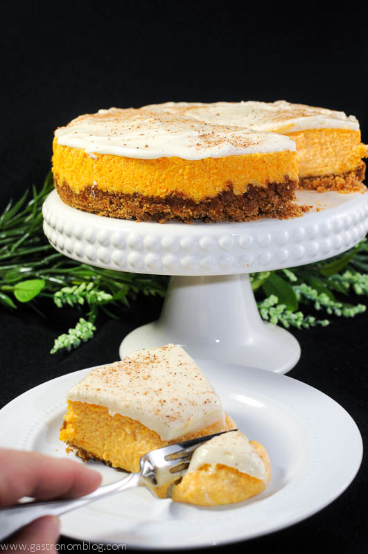 Carrot Cake cheesecake on a white cake stand and a slice being cut on a white plate. Flowers in background