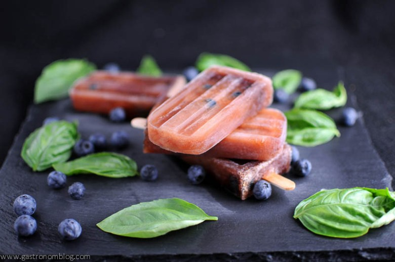 Chianti Icepops with blueberries and basil leaves on a slate