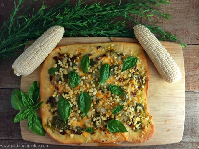 Sausage Corn and Pesto Pizza with ears of corn and basil on a cutting board