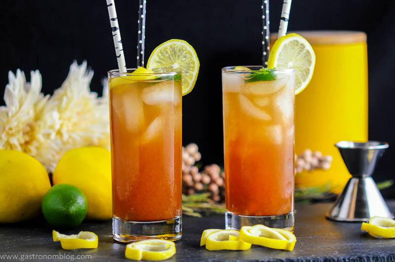 Two tall glasses of Tomato Water Bloody Mary Cocktails made with vodka, lemon juice and hot sauce, garnished with lemon and lime curls.