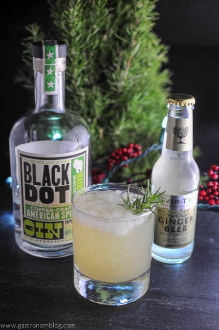 Rosemary's Pear cocktail in a rocks glass with gin bottle and ginger beer bottle with tree in background