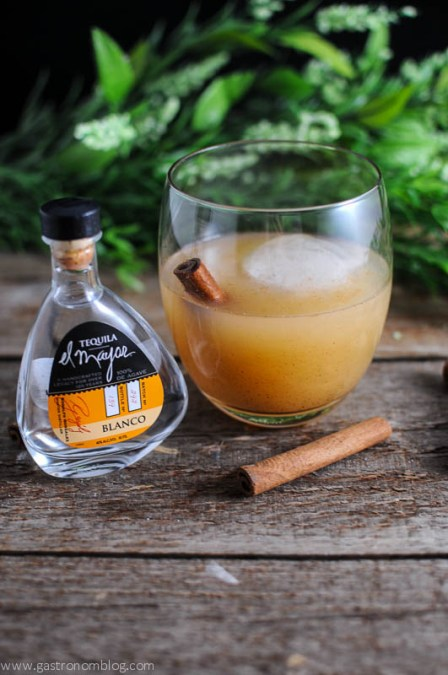 Spiced Pear Tequila cocktail in a glass, with tequila bottle and cinnamon stick