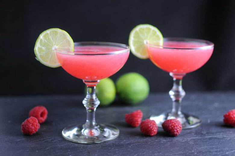 Raspberry Gimlet Cocktail in two coupe glasses with raspberries and limes