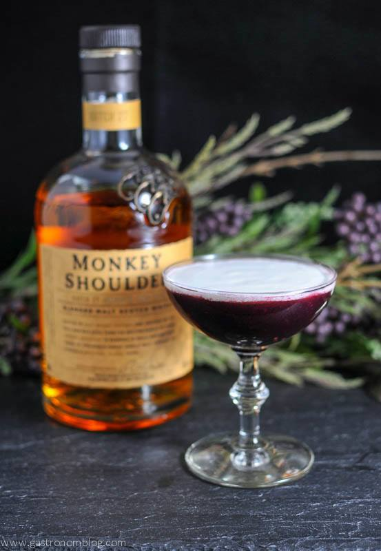 The Black Scot cocktail in a cocktail coupe, Monkey Shoulder whisky bottle and flowers in background
