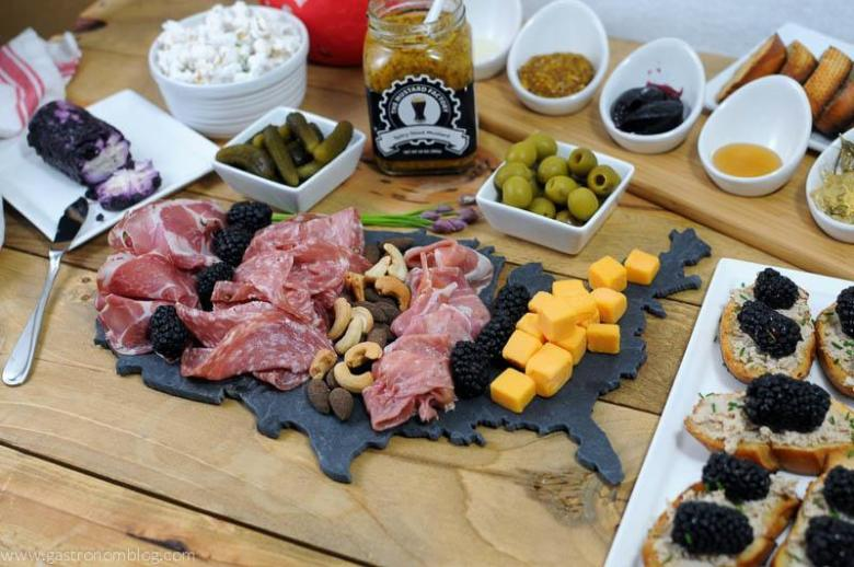 Charcuterie spread on a USA shaped slate board. Cheese, pickles, olives, crostini and spreads in white ceramic containers in the background