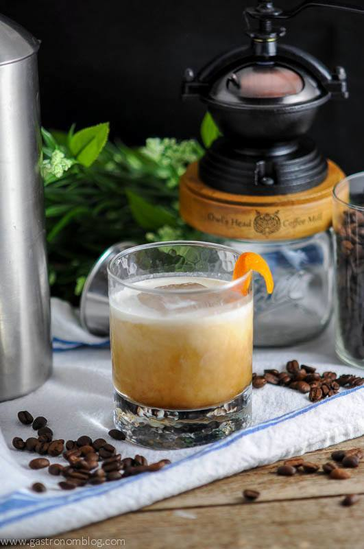 Cold brew coffee cocktail in a rocks glass with cream being poured into it. Coffee grinder, white napkin and coffee beans in the background