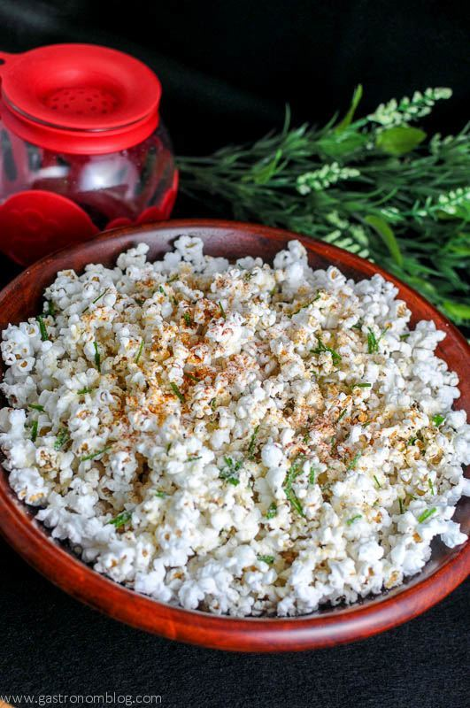 Popcorn in a wooden bowl with popcorn popper in background with flowers
