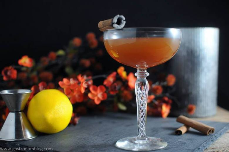 The Clove and Cider Cocktail in cocktail coupe. Metal container, cinnamon sticks, lemon, flowers and jigger in background.