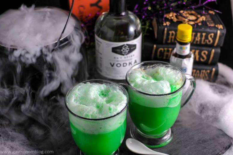 Polyjuice Potion cocktail in glass mugs. Bottle of vodka and bitters in background with cauldron of dry ice and halloween books