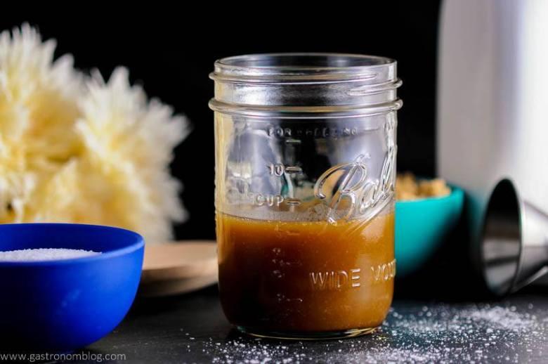 Salted Bourbon Butterscotch Sauce in mason jar, blue bowl of salt, flowers and jigger