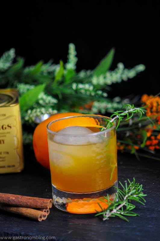 Earl of Orange Cocktail in rocks glass with rosemary, cinnamon sticks, orange and Earl Gray tin in back with flowers