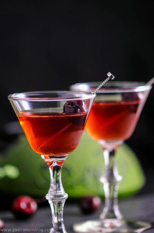 The Cherry Blossom Cocktail in two cocktail coupes with cherries and cocktail picks