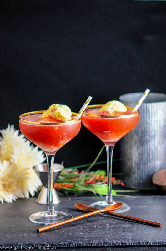 Strawberry Rhubarb Daiquiri Float with ice cream in coupes. Gold dot straws. Wooden spoons. Flowers, jigger and metal container in background