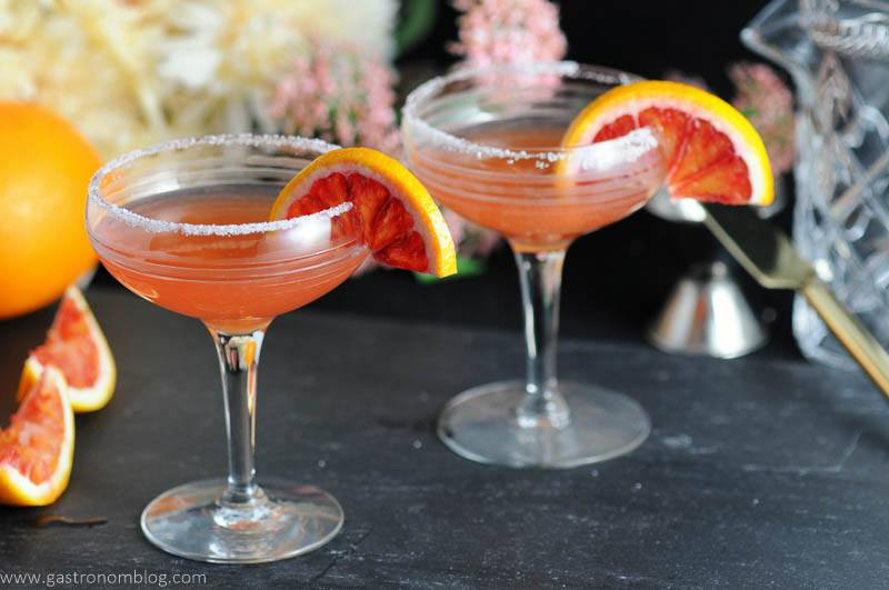 Blood orange sidecars in vintage cocktail coupe and garnished with blood orange wheels.