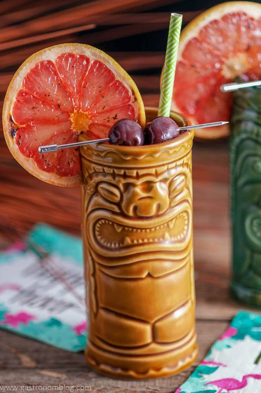 a pair of tiki glasses filled with The Rambler's Ruby, a tiki cocktail garnished with brandied cherries and a bruleed grapefruit.