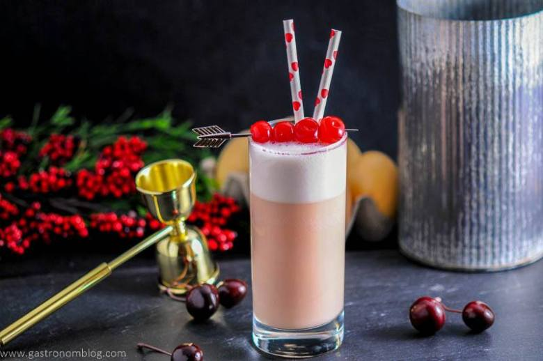 A collins glass sits garnished by maraschino cherries a top a rich foam filled Cherry Toasted Cream Ramos Gin Fizz
