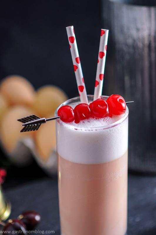 an arrow cocktail pick pieces mraschino cherries that garnish a Cherry Toasted Cream Ramo Gin Fizz