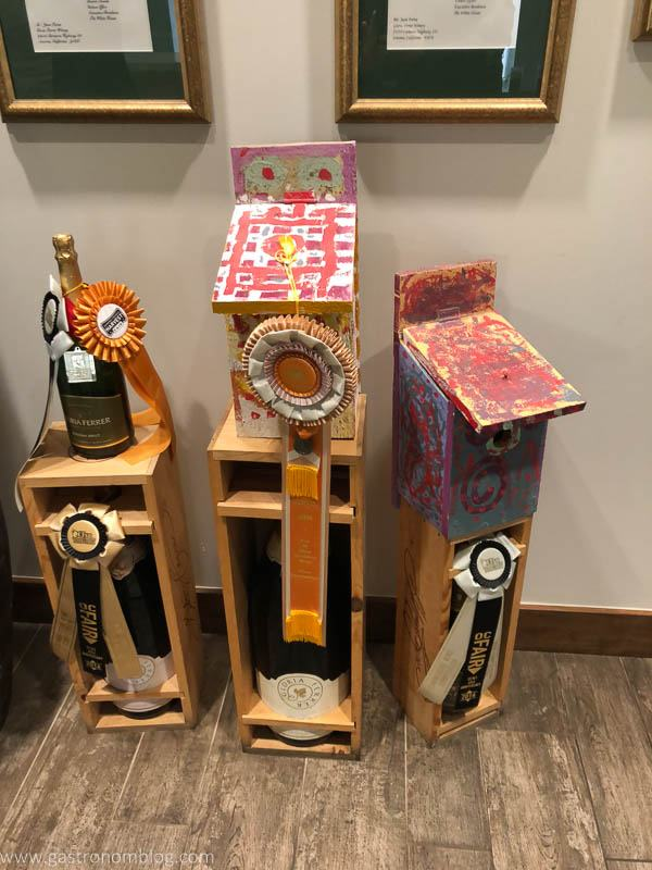 Bottles of wine with awards and painted bluebird houses for charity.