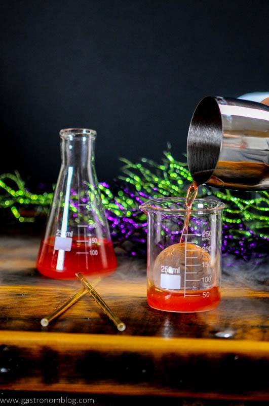 Red Halloween Cocktail being poured into laboratory beakers. Gold straws and silver cocktail shaker.
