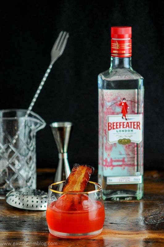 Cocktail in gold rimmed rocks glass with bacon, beefeater bottle behind