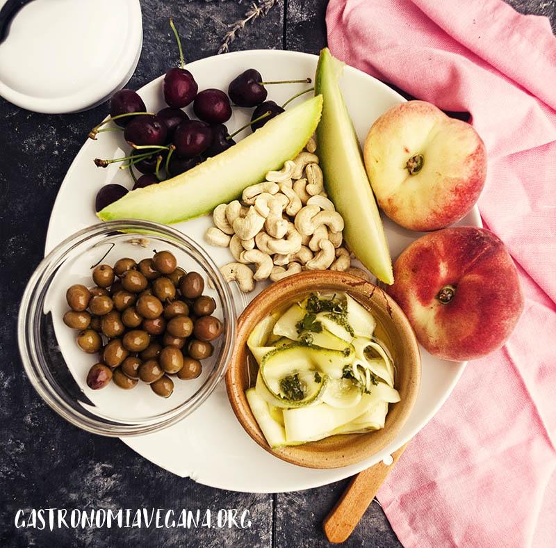 Plato con melón, paraguayos, cerezas, aceitunas, anacardos y calabacín en vinagre