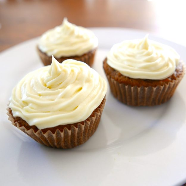 three carrot cupcakes with white cream cheese frosting sitting on a white plate