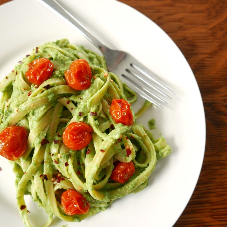 vegan pea pesto fettuccine with red roasted tomatoes on a white plate with a silver fork, sitting on a wooden table
