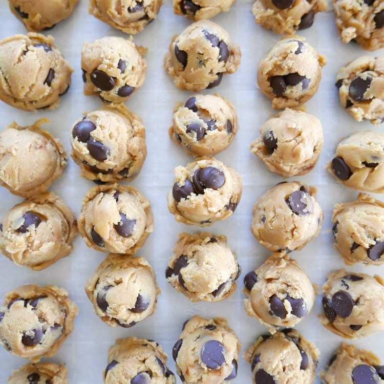 brown butter chocolate chip cookie dough arranged in five rows on a baking sheet