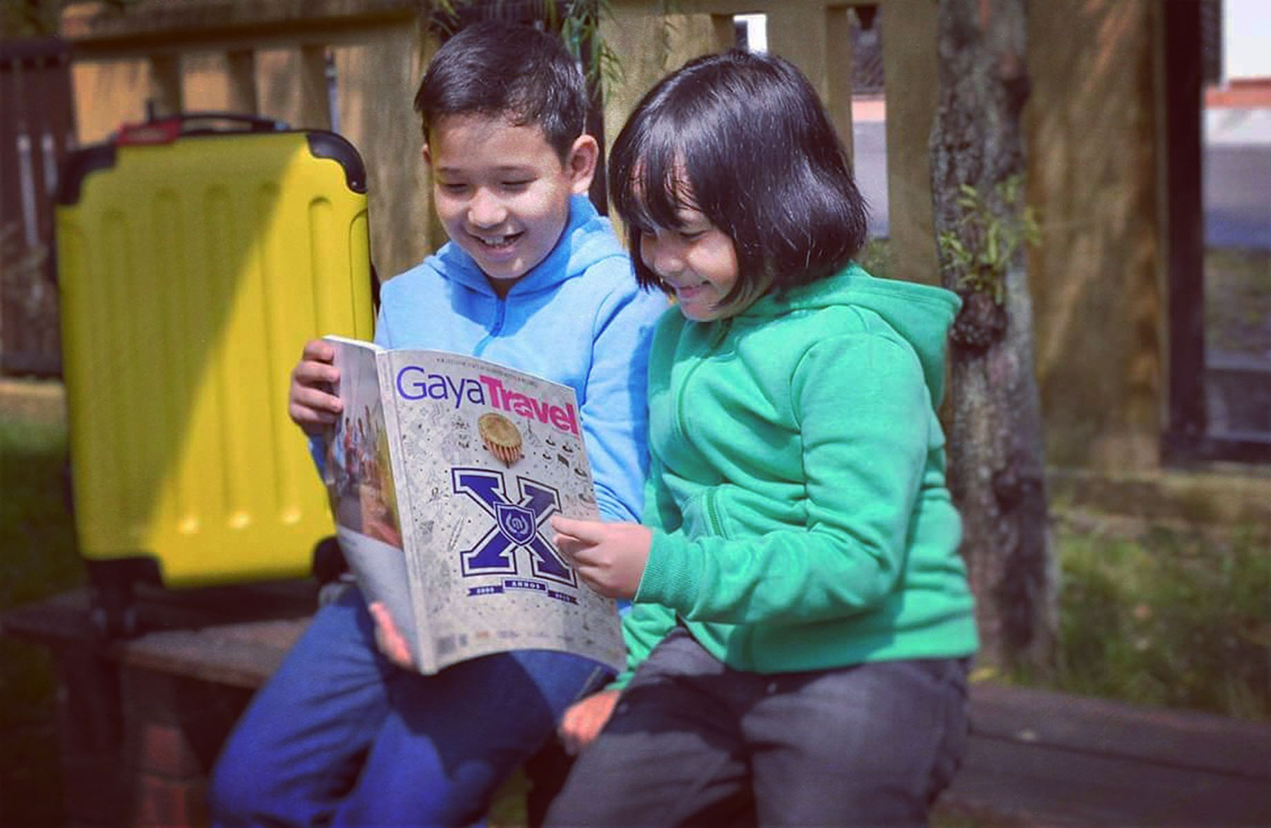 Young boy and girl are reading Gaya Travel Magazine
