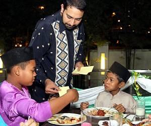 Silka Johor Bahru's General Manager Ramanesh Keith Nair handing out Raya packets to the children.